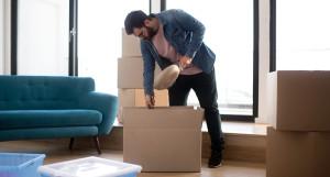 ragazzo che riempie uno scatolone per trasloco